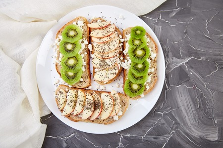 Healthy breakfast toasts with kiwi, apple, cottage cheese and chia seeds on white plate and grey background. Top view, flat lay. Diet food. Vegan. 스톡 콘텐츠