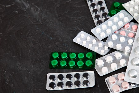 Pills, tablets and blister on black background. Health care concept. Flat lay. Copy space.