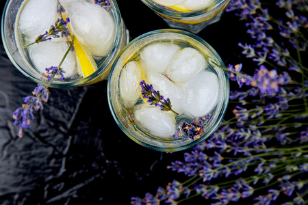 Lavender lemonade with lemon and ice on black background. Detox water. Summer drink. Diet cocktail. Beautiful. Top view. Copy space. 写真素材