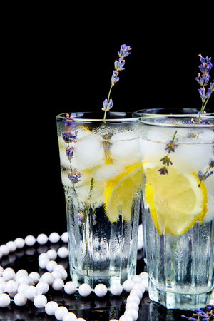 Lavender lemonade with lemon and ice on black background. Detox water. Summer drink. Diet cocktail. Beautiful.