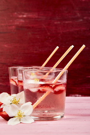 Strawberry detox water with jasmine flower. Summer iced drink or tea. Lemonade with berry. Flavored Water in glasses with Fresh Strawberry. Diet. 스톡 콘텐츠
