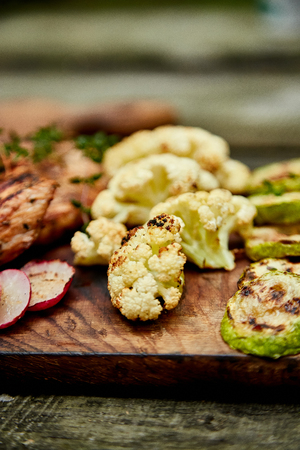 Grilled zucchini and cauliflower vegetable on wooden background . Vegan food. Diet, healthy Picnic. Summer. Top view. Flat lay. Copy space. 免版税图像