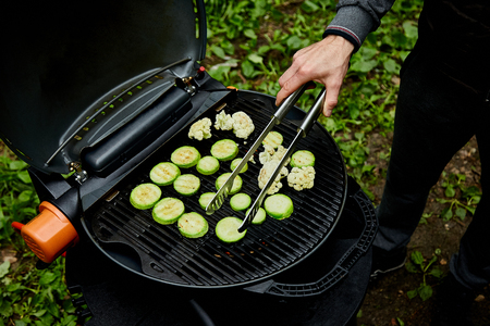 Hand of young man grilling zucchini vegetable on huge gas grill . Picnic. Summer. Top view. Flat lay. Copy space. Фото со стока - 122692429