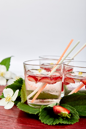 Strawberry detox water with jasmine flower. Summer iced drink or tea. Lemonade with berry. Flavored Water in glasses with Fresh Strawberry. Diet. Stockfoto