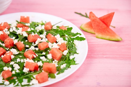 Fresh summer watermelon salad with feta cheese and arugula on pink table background. Vegan food. Diet, Vegetarian.Copy space
