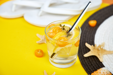 Holidays and drink concept. Cold cocktail, lemonade with lemon and kumquat, mint  in a glass on a yellow table. Summer background. Detox water.