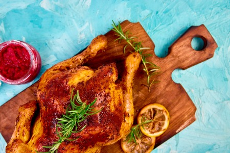 Baked whole chicken with sauces on wooden board on blue Stok Fotoğraf