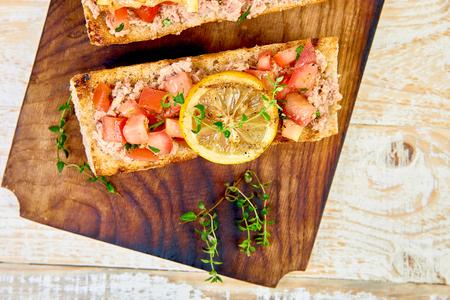 Appetizer bruschetta with tuna and tomatoes. Italian cuisine. Delicious Italian antipasti crostini on wooden board. Copy space. Top view.