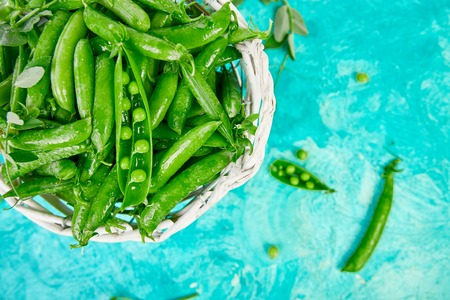 White Basket with fresh green peas on blue background. Vegan and vegetarian food concept. Flat lay. Imagens