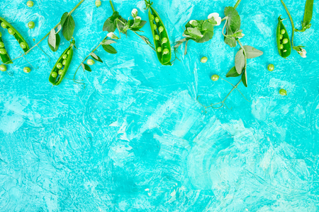 Flat lay composition with delicious fresh green peas on blue background. Vegan and vegetarian food concept.