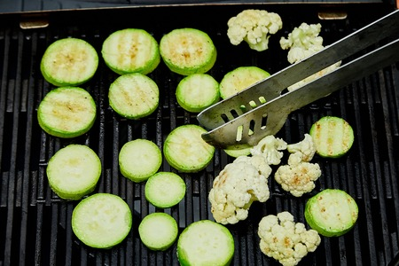 Hand of young man grilling zucchini vegetable on huge gas grill . Picnic. Summer. Top view. Flat lay. Copy space.