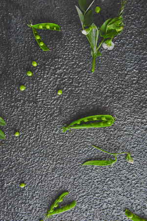 Flat lay composition with delicious fresh green peas on black background. Vegan and vegetarian food concept. Imagens