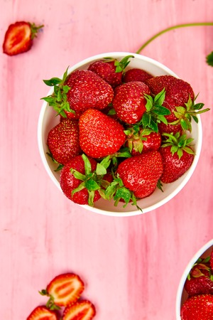 Ripe red strawberries on pink table, Strawberries in white bowls. Fresh strawberries. Beautiful strawberries. Diet food. Healthy, vegan. Top view. Flat lay.