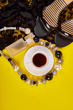 Fashion feminine blogger concept. Minimal set of women accessories with cup of coffee on yellow background. Still life perfume, jewellery, shoes, lace dress. copy space for text. Flat lay