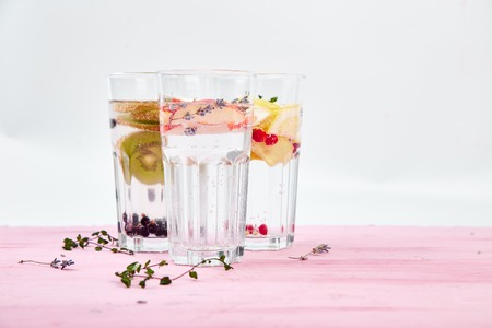 Variety of  Detox infused water with  kiwi, apple, lavender, ginger, lemon, mint on pink background. Refreshing summer homemade cocktail. Diet. Healthy drink. Copy space. Imagens