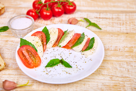 Italian caprese salad with sliced tomatoes, mozzarella cheese, basil, olive oil on wooden background. Top view with space for your text