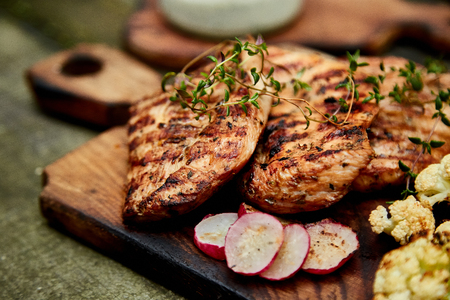 Grilled turkey meat. Steak turkey grill on wooden cutting board with a variety of grilled vegetables on  rustic background  Top view. Flat lay. Copy space.