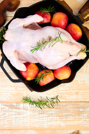 Whole raw chicken in skillet  or iron pan with rosemary leaf, thyme, lemon, red apples . Ready to cook. Cooking background. Copy space Imagens