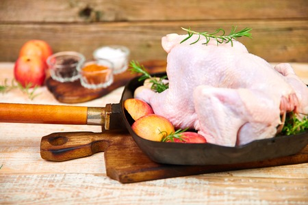 Whole raw chicken in skillet  or iron pan with rosemary leaf, thyme, lemon, red apples . Ready to cook. Cooking background. Copy space Stockfoto
