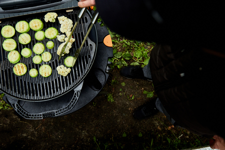 Hand of young man grilling zucchini vegetable on huge gas grill . Imagens