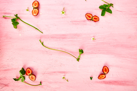 Flat lay composition with strawberries on a pink background.