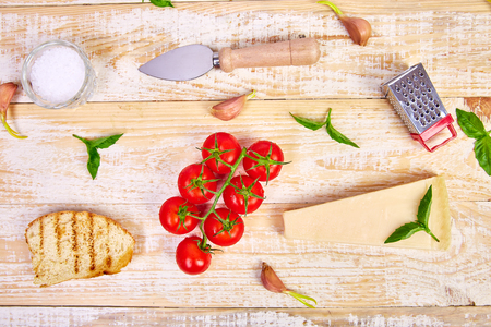 Italian food ingredients, with vine tomatoes, basil, parmesan, olive oil, garlic, bread on wooden background Ready for cooking. Top view, view from above. Copy space. Flat lay. Food frame Imagens