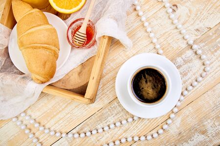 Good morning.Continental breakfast on ristic wooden background. Cup of coffee, orange juice, croissants, jam on wooden tray from above. Top view.  Flat lay. Copy space. Layout