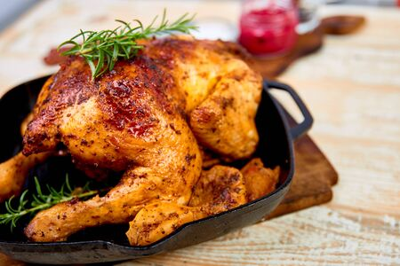 Baked whole chicken with apples in pan on wooden rustic background. Served on wooden board. Christmas chicken. Reklamní fotografie