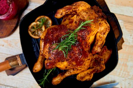 Baked whole chicken with apples in pan