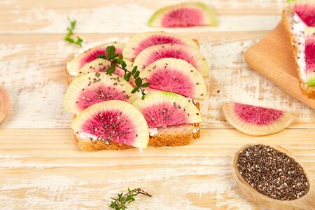 Healthy breakfast toasts from sliced watermelon radish or chinese daikon, chia and cottage cheese on board wooden background. Copy space.