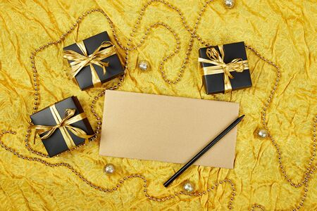 Pile of handmade luxury black gift boxes with gold ribbon DIY decoration, blank sheet paper for greeting text,  gold wedding invitation. Birthday, christmas holiday concept. Copy space. Top view. Flat design. Flat lay.
