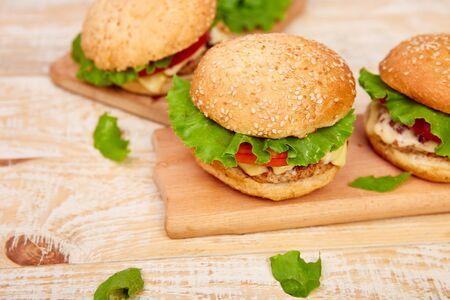 Hamburguesa de ternera artesanal en mesa de madera sobre fondo claro. Comida callejera, comida rápida. Jugosas hamburguesas caseras con queso y sobre la mesa de madera. Copie el espacio. Foto de archivo
