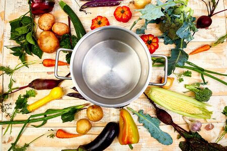 Various organic vegetables ingredients around empty cooking pot on old wooden table, top view. Flat lay. Stock Photo
