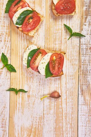 Caprese bruschetta toasts. Bruschetta with tomatoes, mozzarella cheese and basil on a rustic table. Traditional italian appetizer or snack, antipasto Imagens