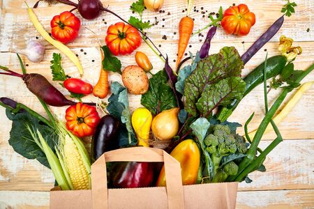 Paper bag of different health vegetables food on wooden background. Top view. Flat lay Beige canvas grocery bag fallen over while dropping vegetables.