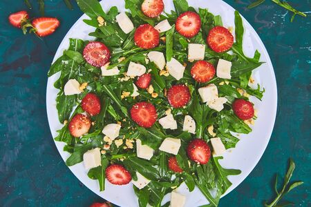 Fresh salad with arugula, strawberries, feta cheese and nuts on green background. Vegetarian. Diet food. Italian food. Top view. Copy space.