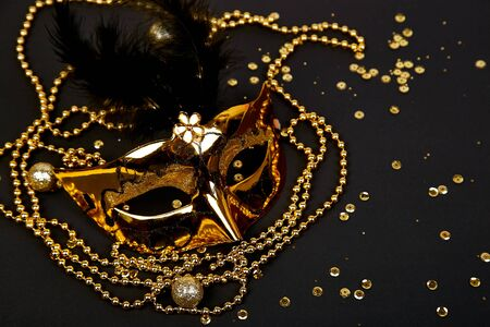 Black and gold carnival mask. Top view image of masquerade background. Flat lay. Mardi Gras celebration concept. Copy space. Фото со стока
