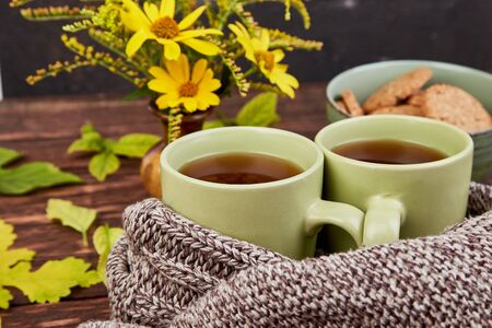 Knitted scarf with two warm cups of tea cookies, autumn leaves on wooden table. Autumn. Fall season. Still life. Фото со стока