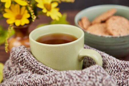 Knitted scarf with warm cup of tea and cookies, autumn leaves on wooden table. Autumn. Fall season. Still life. Фото со стока