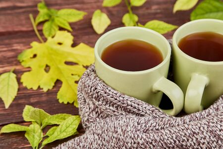 Knitted scarf with two warm cups of tea, autumn leaves on wooden table. Autumn. Fall season. Still life.