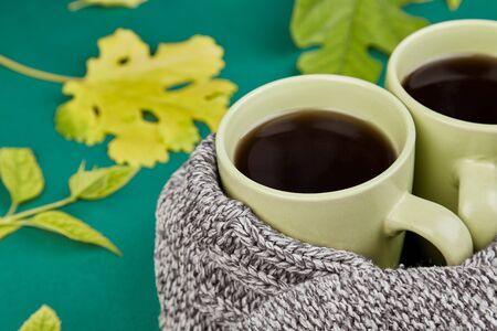 Knitted scarf with two warm cups of tea, autumn leaves on green background, Autumn. Fall season. Still life.