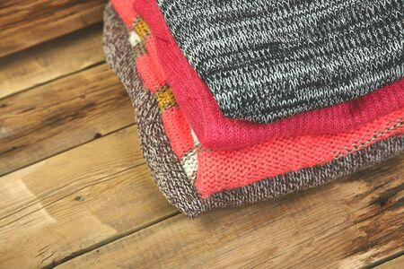 Stack of cozy knitted sweaters. A pile of warm sweaters on a wooden table on rustic background. Autumn and winter clothes. Copy space.