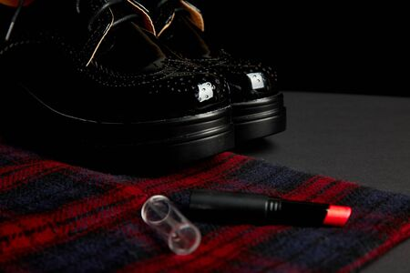 Autumn stylish womans outfit. Red striped coat, black oxford shoes and  lipstick on black background. Top view. Flat lay. Copy space.