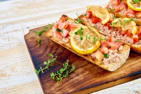 Appetizer bruschetta with tuna and tomatoes. Italian cuisine.