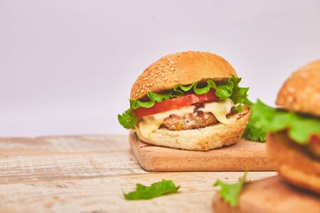 Craft beef burger on wooden table on light background