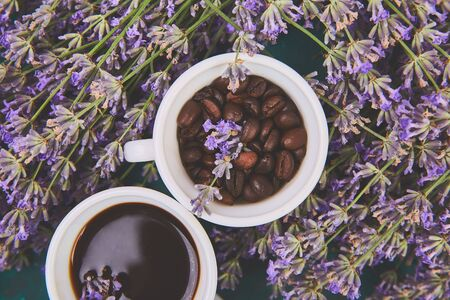 Coffee, coffee grain in cups and lavender flower on green background from above. Good Morning concept. Woman working desk. Cozy breakfast. Mockup. Flat lay style