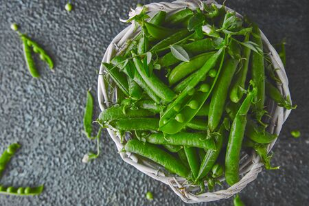 White Basket with fresh green peas on black background. Vegan and vegetarian food concept. Flat lay.