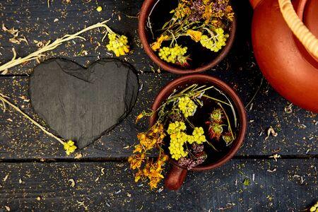 Two Cup of herbal tea tutsan, sagebrush, oregano, helichrysum, lavender near brown teapot on dark wooden background. Herbal tea.Flat lay. Hear. Love.