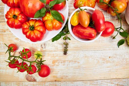 Mix of tomatoes background. Beautiful juicy organic red tomatoes on white wooden table background. Clean eating concept. Copy space, flat lay.