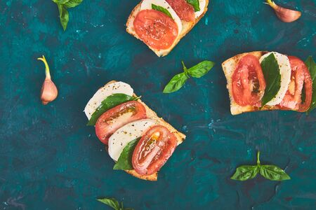 Caprese bruschetta toasts. Bruschetta with tomatoes, mozzarella cheese and basil on a green background. Traditional italian appetizer or snack, antipasto Фото со стока